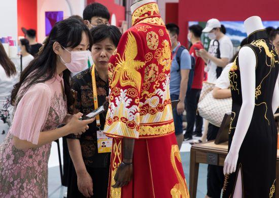 消博会上,观众被制作精良的传统服装吸引。新华社发