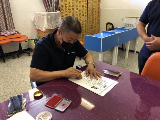 加纳利华人华侨协会志愿者为审核合格的材料加盖协会印章