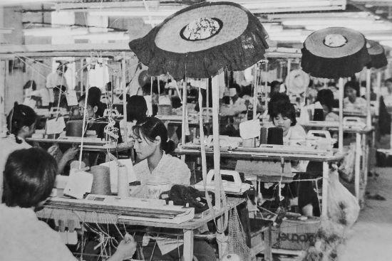 1982年,东莞,在珠三角的服装厂,客家女特有的裙式遮阳帽子挂在工作台上方。