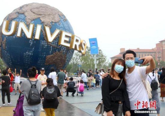 9月5日,游客在北京环球度假区的标志性景观前拍照留影。中新社记者 易海菲 摄