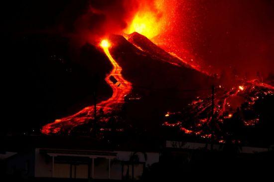 喷出的岩浆在黑夜中照亮当地上空