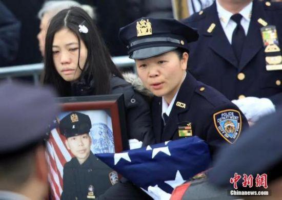 资料图:刘文健的遗孀在华裔女警的陪伴下手捧刘文健的遗像走出殡仪馆,准备护送刘警探的灵柩赴墓地安葬。中新社发 阮煜琳 摄